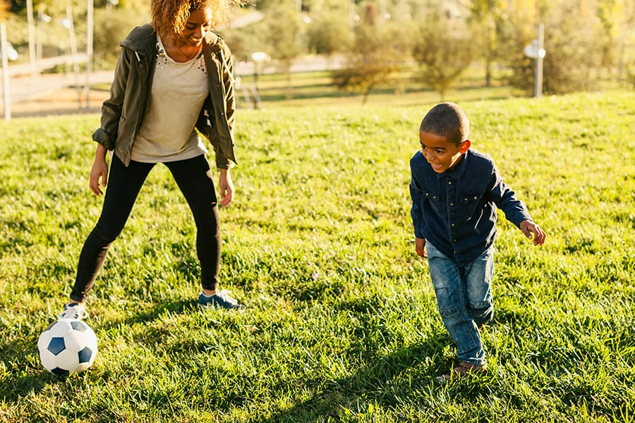 Adult and child in sunny, grassy field playing with soccer ball.
