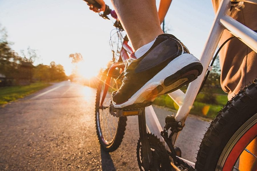 Closeup of persons shoe pedalling a bike down a paved path lined with trees into bright sunshine.