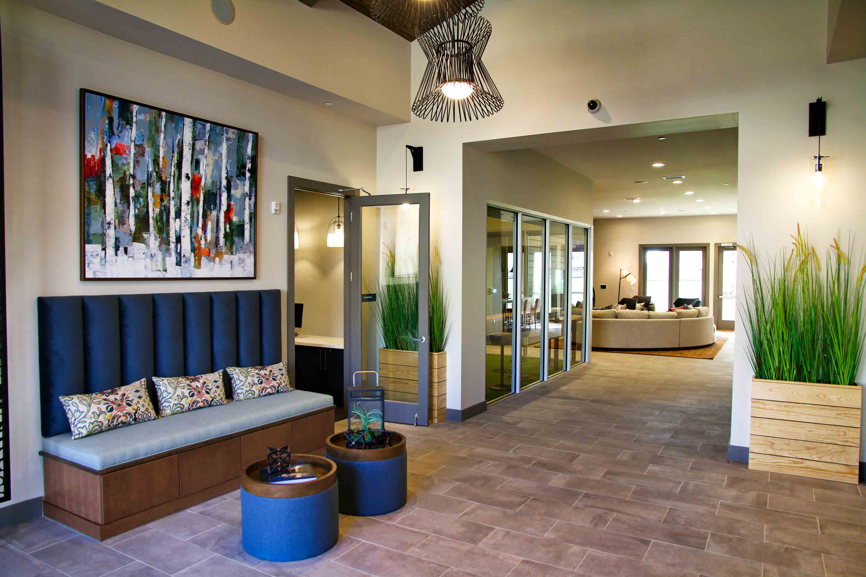 Entrance lobby with tiled floors, plush bench seat, wood planters with tall grasses, and modern chandelier.