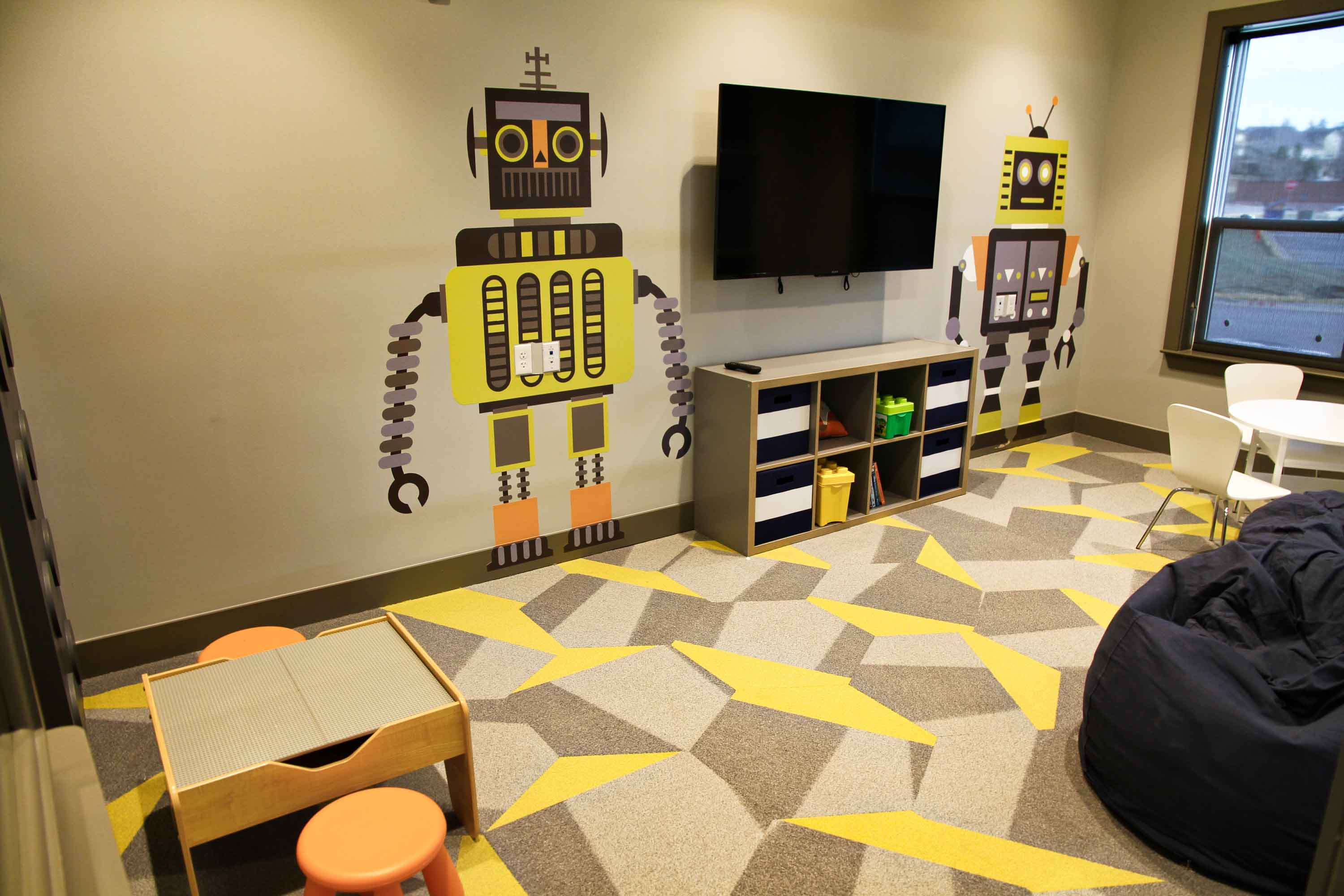 Childrens play area with robot wall graphics, geometric pattern carpet, wall mounted TV and large beanbag chair.