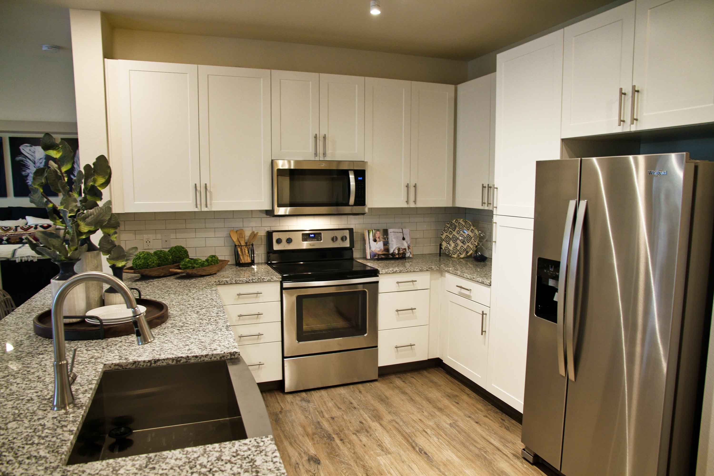 Kitchen with hardwood style floors, smooth granite countertops, and stainless steel farmhouse sink and appliances.