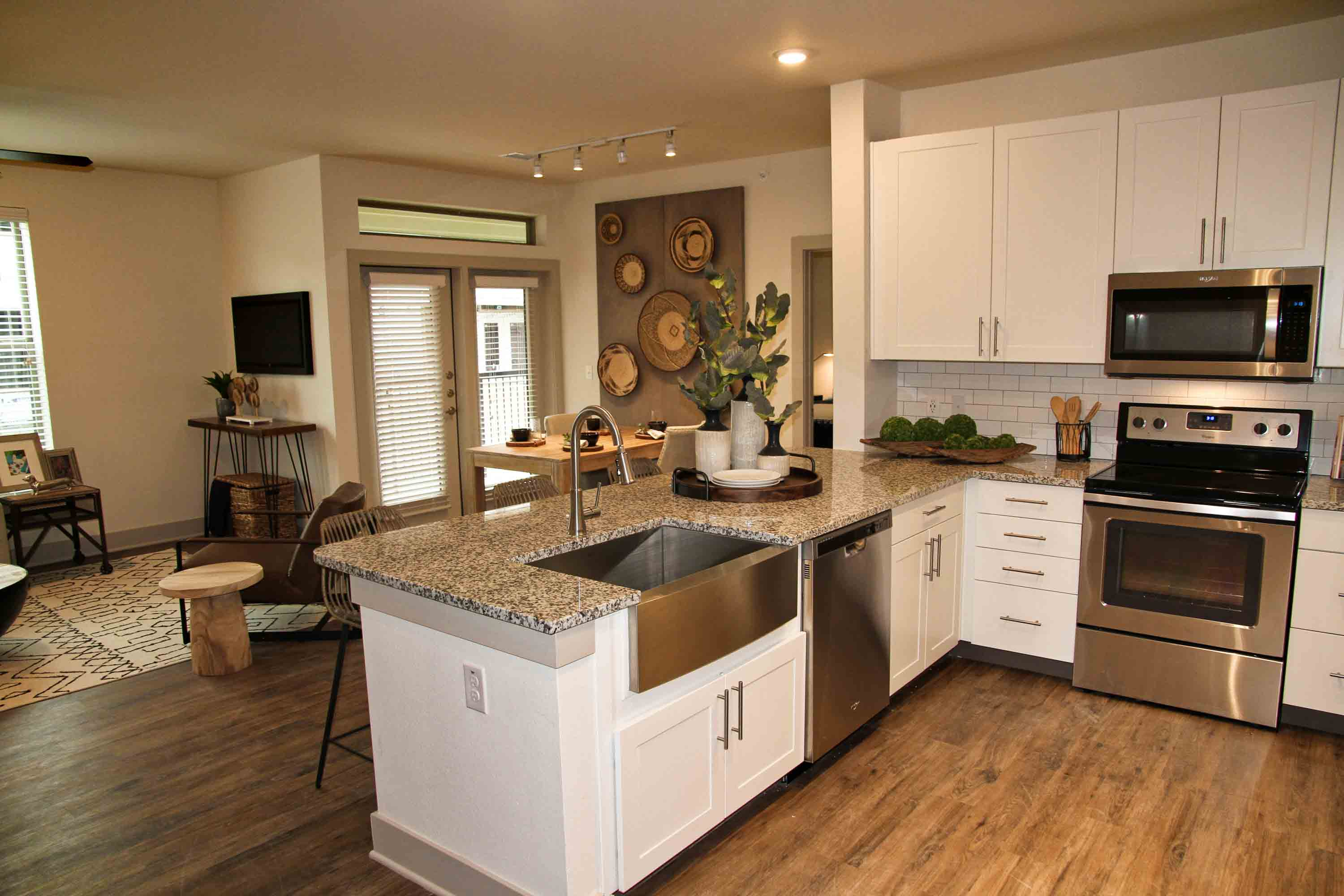 Kitchen and living area with hardwood style floors, granite countertops, and large glass balcony doors with natural light.