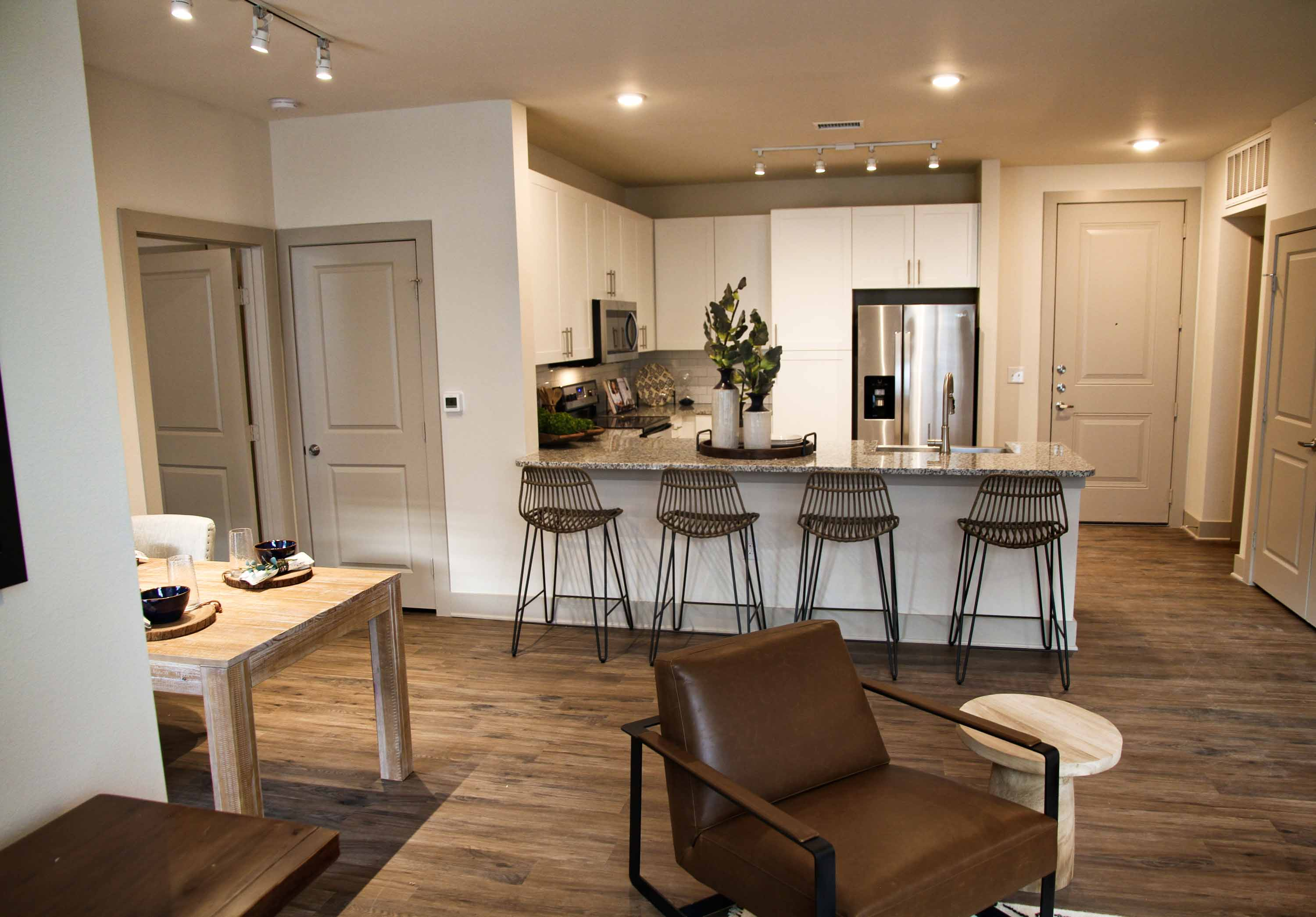 Kitchen and living area with hardwood style floors, tall breakfast bar, dining table, and bright directional lighting.