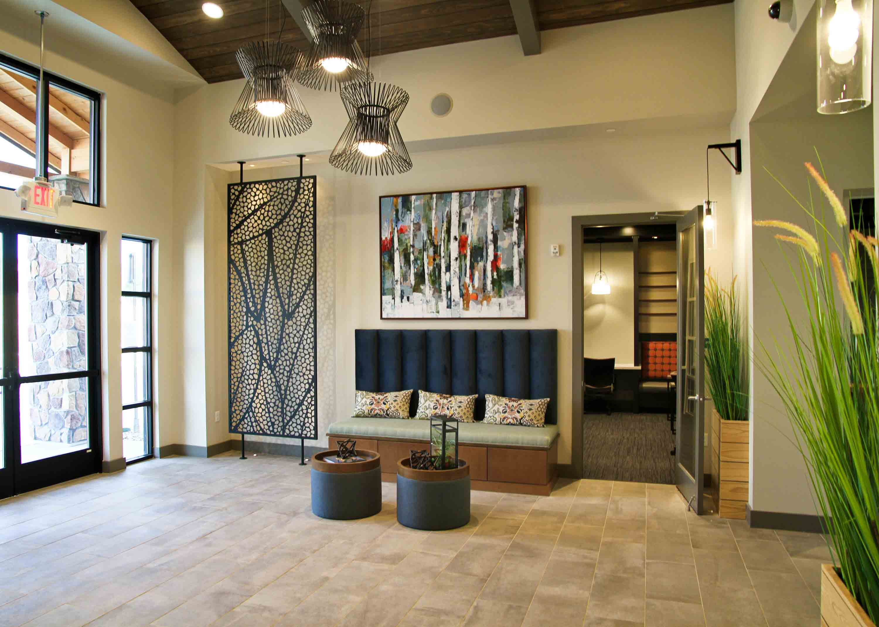 Lobby area with plush bench seat, round ottomans with terrarium, metal wall decor, and modern chandelier.