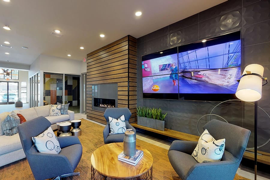 Community room with large wall mounted TV, wide modern fireplace, and plush fabric sectional and chairs with pillows.