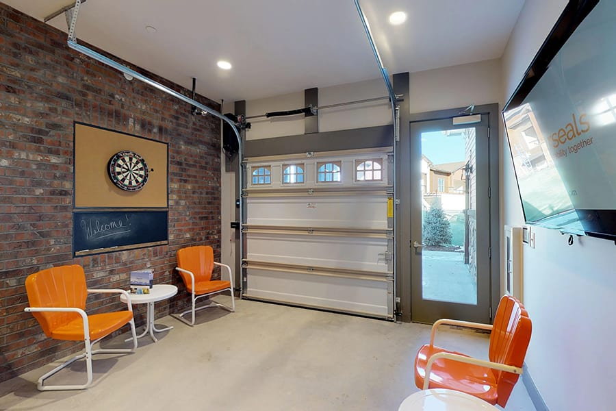 Bicycle repair room with chairs, dartboard hung on brick wall, wall mounted TV, and garage door.