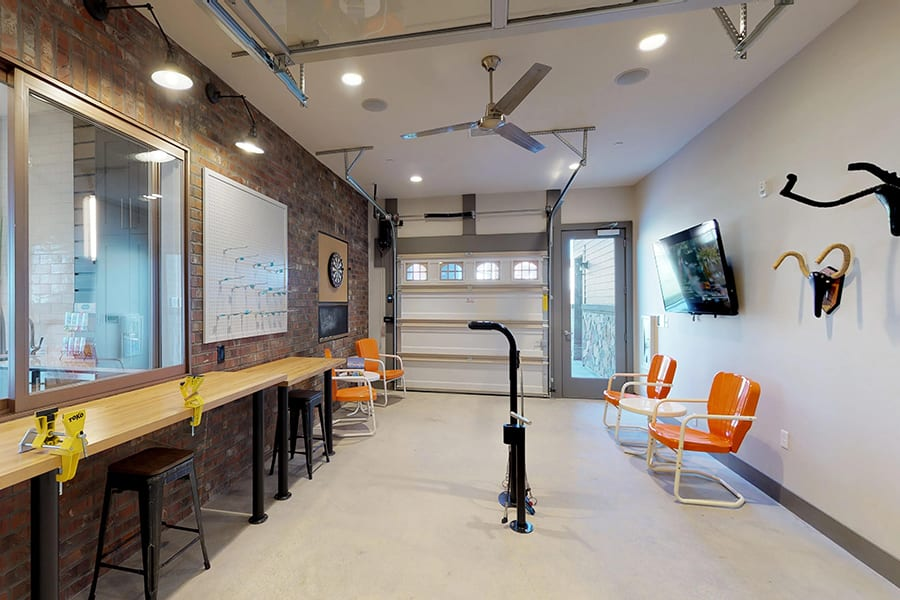 Bicycle repair room with tall wood work benches, bike stand, wall mounted TV and garage door.
