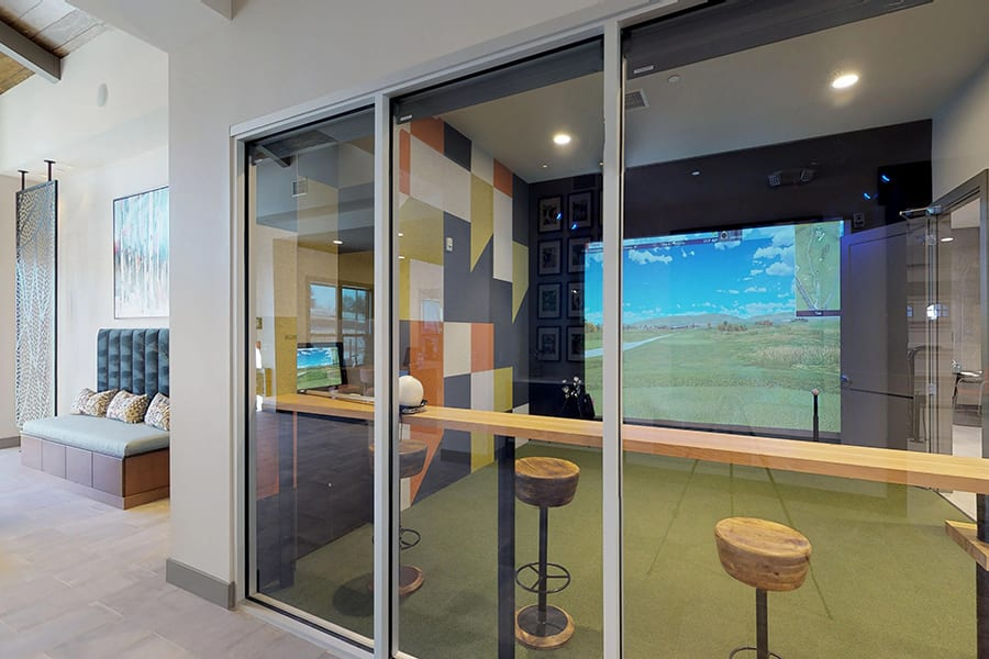 Clubhouse hallway looking through windows into gaming room with large simulator screen and bar seating area.