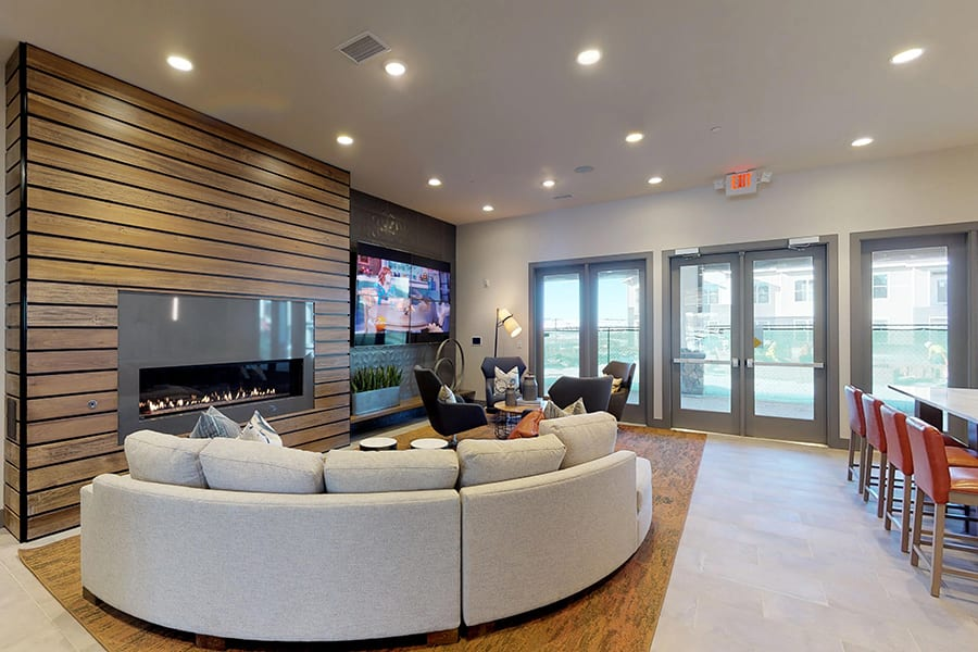 Clubhouse community room with large wall mounted TV, round fabric sectional couch, and tall windows with natural light.