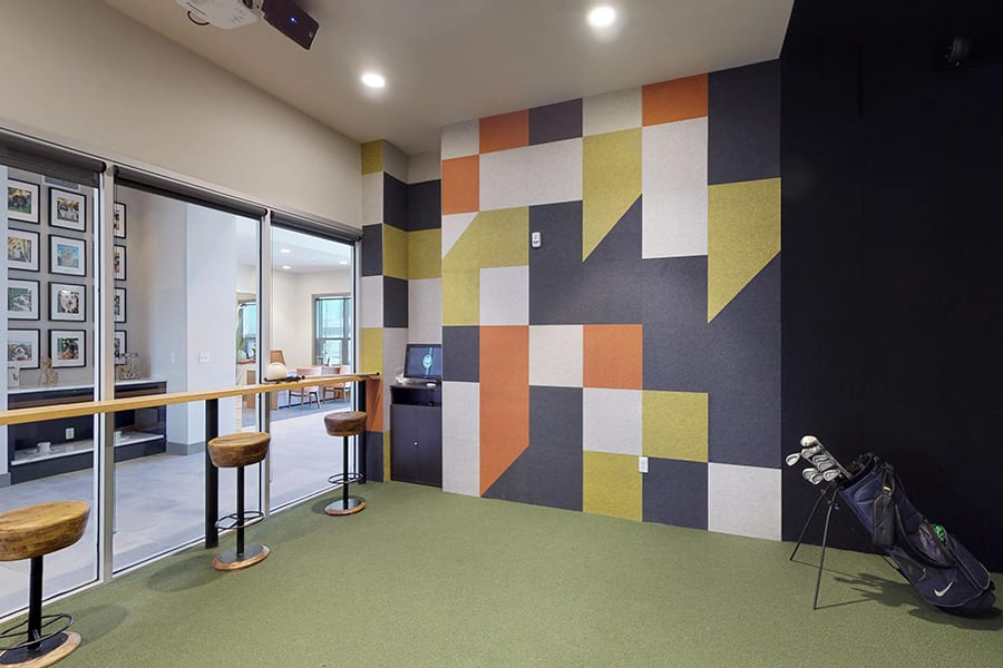 Gaming room with geometric painted wall pattern, bag of golf clubs, and bar seating area.