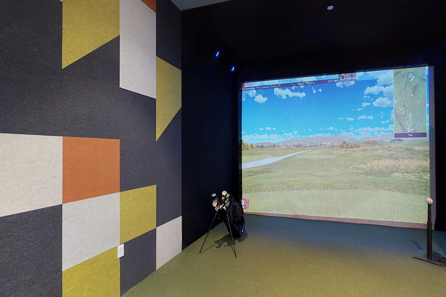 Gaming room with large simulator screen, bag of golf clubs, baseball on hitting tee, and geometric wall pattern.