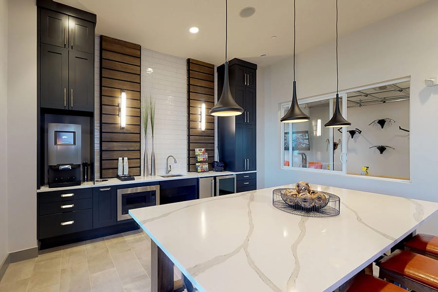 Clubhouse kitchen with large dining table, hanging pendant lights, and stainless steel touchscreen coffee machine.