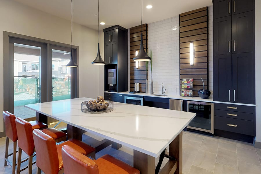 Clubhouse kitchen with large dining table, smooth countertops, and stainless steel refrigerator and microwave.