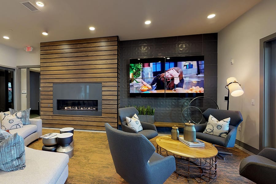 Clubhouse community room with large wall mounted TV and circular fabric sectional couch in front of modern fireplace.