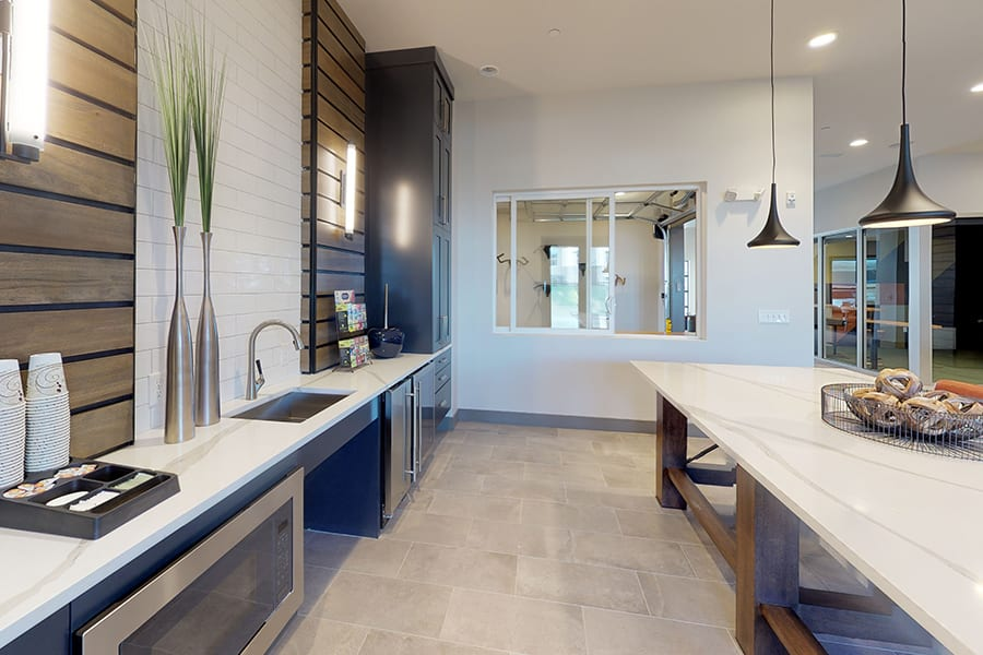 Clubhouse kitchen with tile floors, smooth countertops, stainless steel appliances, and large table with pendant lights.