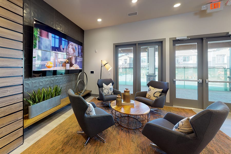 Clubhouse community room with large wall mounted TV, plush fabric chairs with coffee table, and tall windows with natural light.