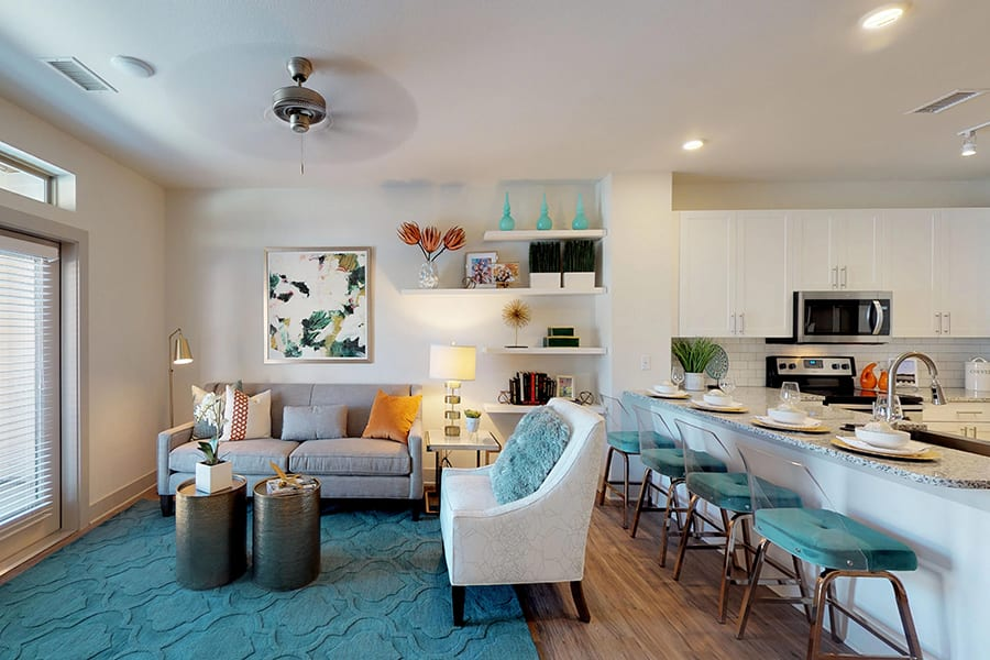 Living area with plush fabric seating, hardwood style floor with textured rug, ceiling fan, and shelves with decorations.