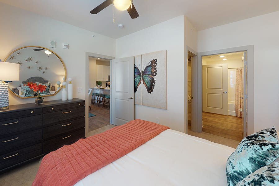 Bedroom with large bed, lighted ceiling fan, rich wood dresser, and doors to living area, walk in closet, and bathroom.
