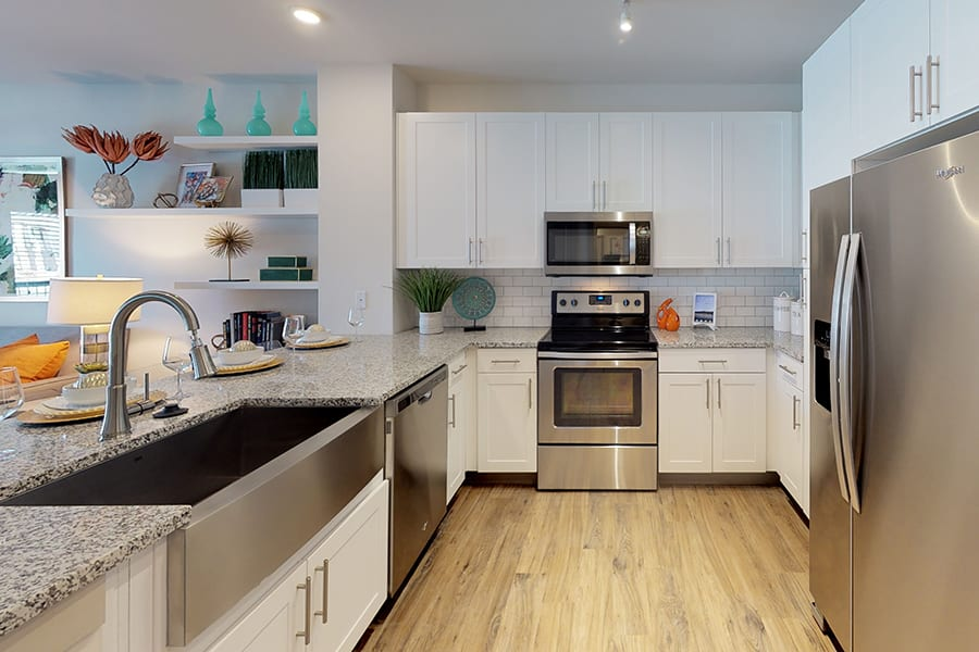 Kitchen and living area with granite countertops, stainless steel farmhouse sink and appliances, and decorated shelves.