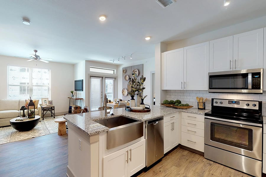 Kitchen and living area with smooth granite countertops, stainless steel farmhouse sink and appliances, and large windows.