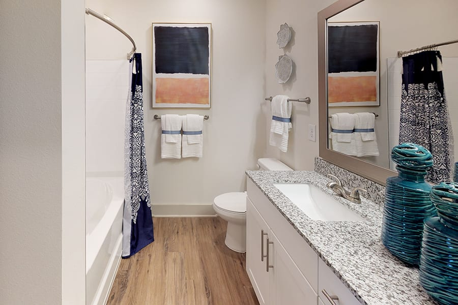 Bathroom with hardwood style floors, granite countertop, tub and shower with curtain, and large vases.