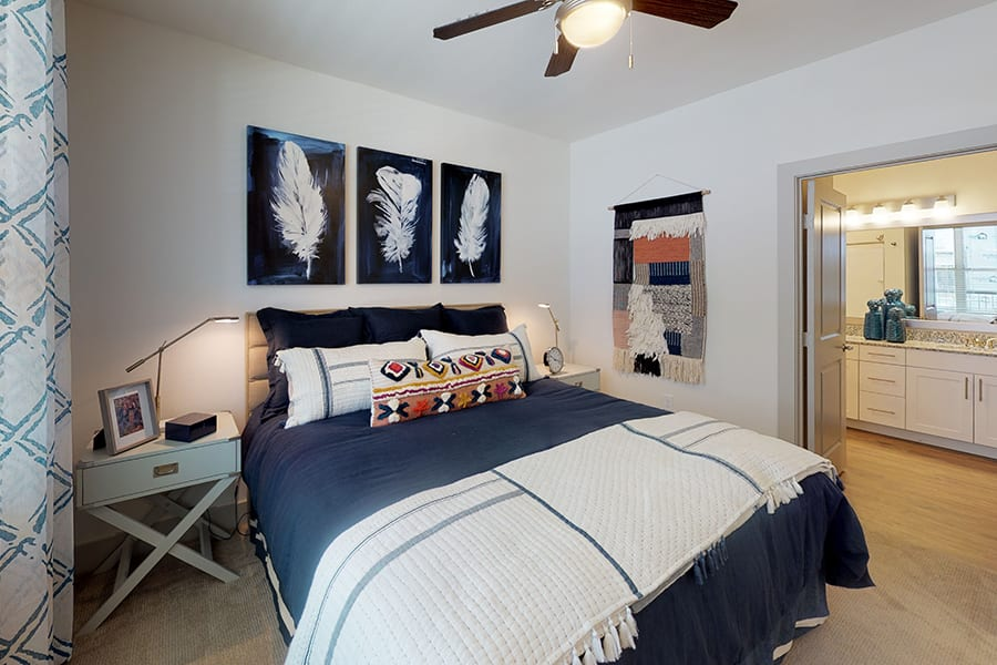 Bedroom with carpet, bed with plush comforter and pillows, lighted ceiling fan, and double doors into adjoining bathroom.