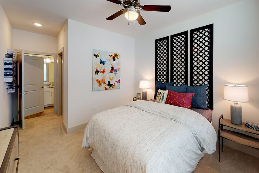 Bedroom with carpet, bed with plush comforter and pillows, bedside tables with lamps, and lighted ceiling fan.