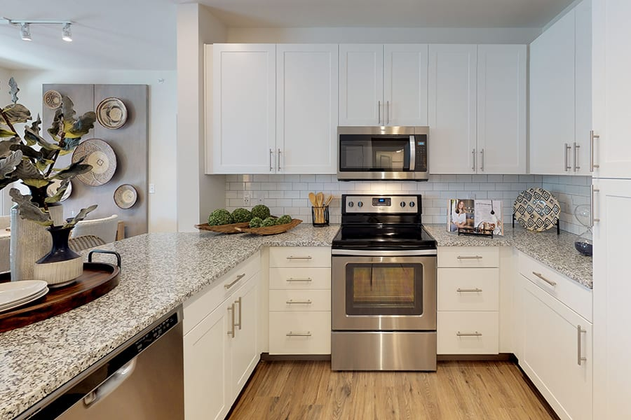 Bright kitchen with smooth granite countertops, stainless steel appliances, and rich hardwood style floors.