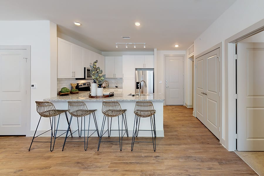 Kitchen with rich wood style floors, breakfast bar with tall seats and smooth granite countertop, and succulent plants.
