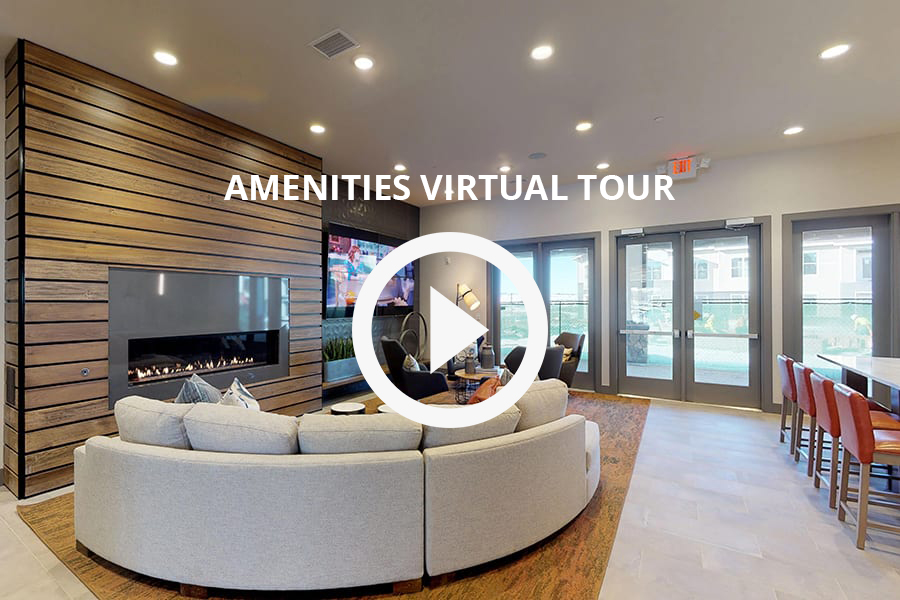 Virtual tour of amenities with wide modern fireplace, large wall mounted TV, and round fabric sectional couch.