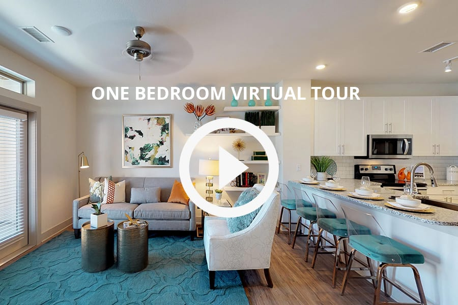Virtual tour of 1 bedroom unit with combined living kitchen space, plush fabric seating, breakfast bar with chairs.