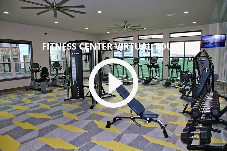 Virtual tour of fitness center with cardio and weight machines, dumbbell rack, and tall windows with natural light.