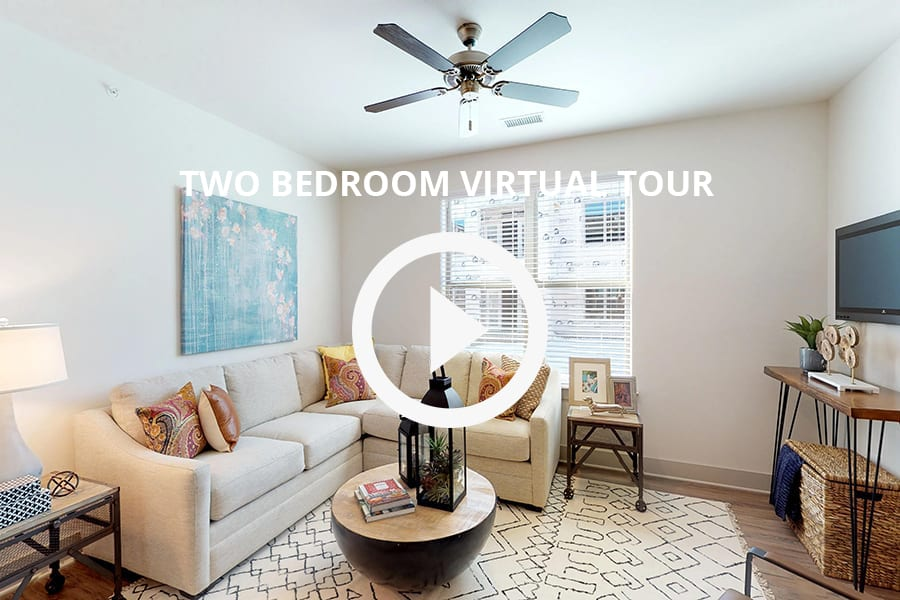 Virtual tour of 2 bedroom unit with plush fabric sectional, hardwood style floors, and bright natural light from window.